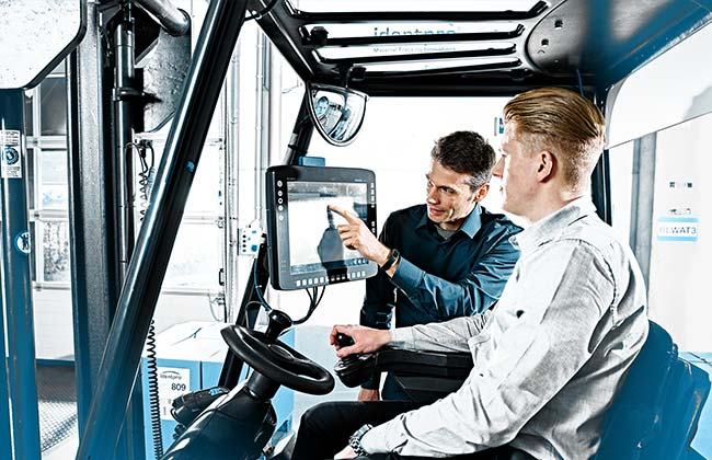 Bild zeigt zwei Personen am Staplerterminal des 3D Staplerleitsystems identpro® TRACK