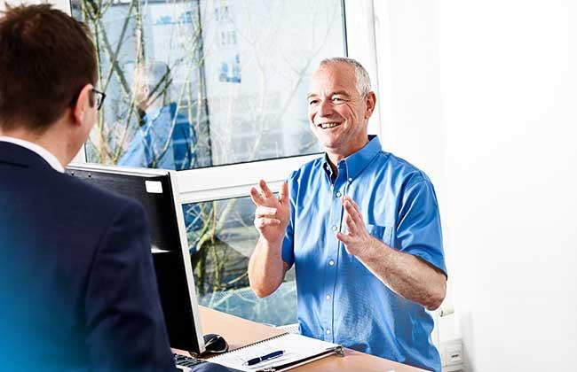 Bild zeigt IdentPro Mitarbeiter mit Spaß an ihrer Arbeit im konstruktiven Dialog