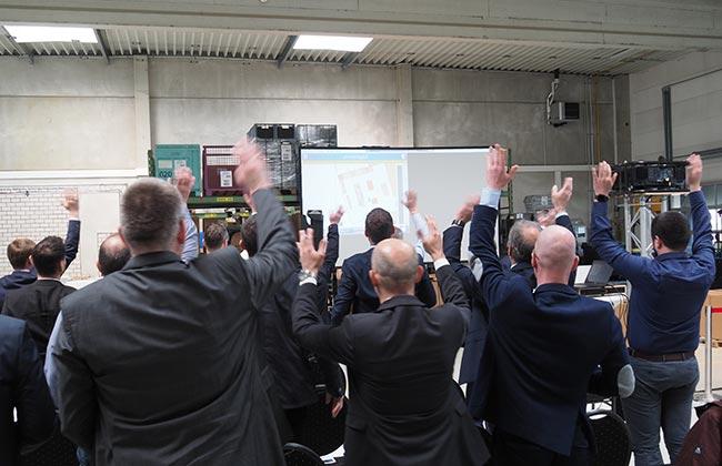 Bild zeigt begeisterte Besucher bei einer Veranstaltung zu scan-freier Intralogistik im IdentPro Technikum