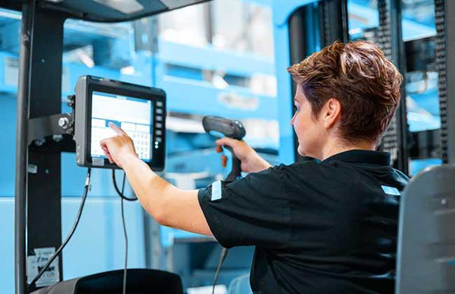 Bild zeigt Frau scannt: Ohne 3D Staplerleitsystem identpro TRACK müssen Staplerfahrer bei SAP EWM scannen